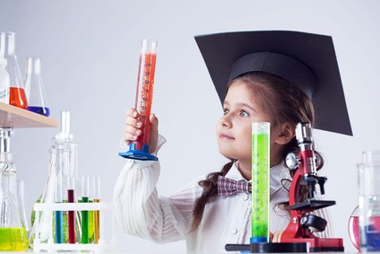 Smart little experimenter looking at test tube, close-up